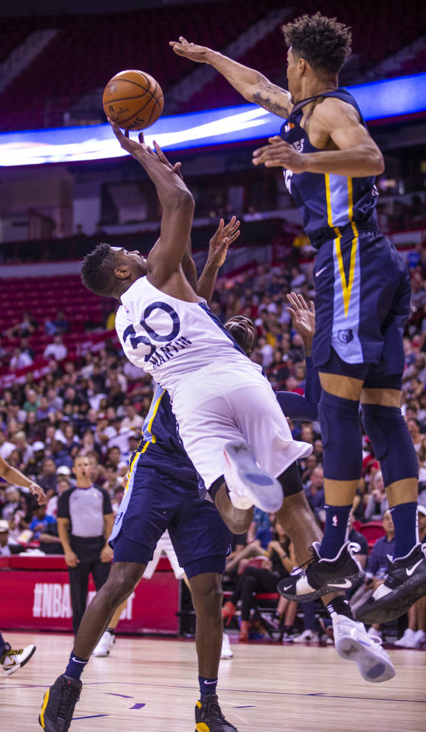 Minnesota Timberwolves forward Kelan Martin, left, releases a shot that will be blocked by Memp ...