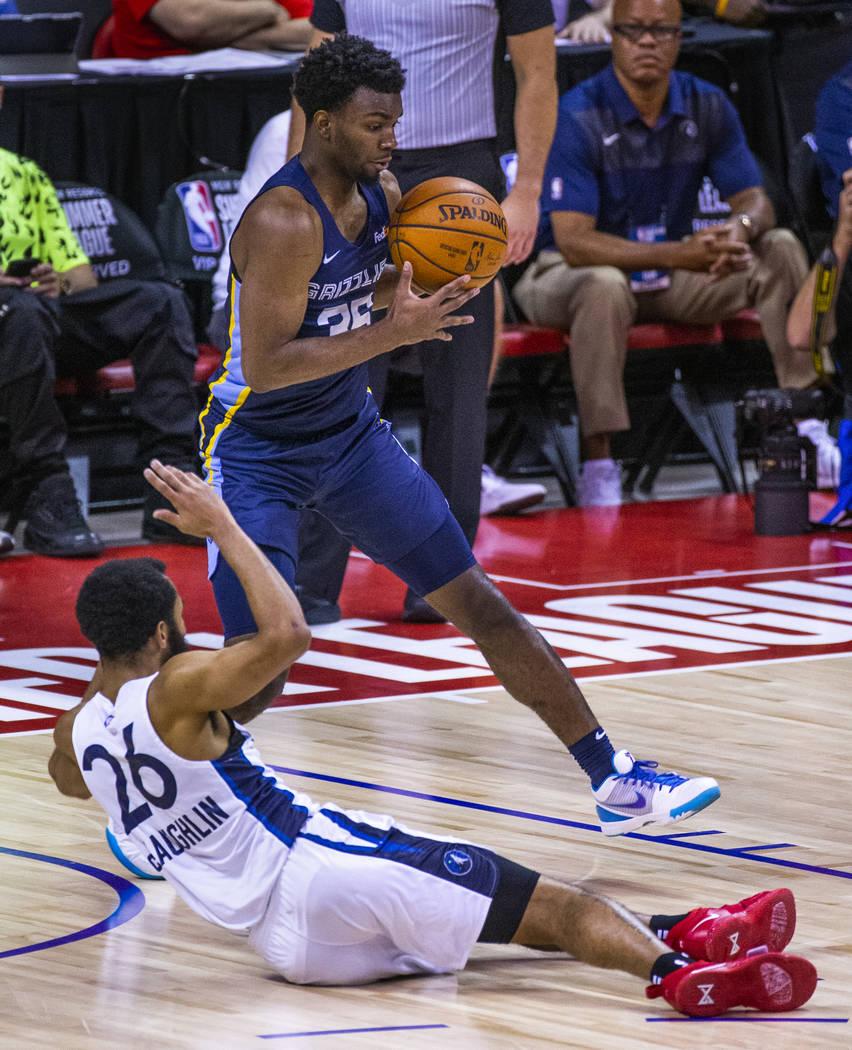 Memphis Grizzlies guard Keenan Evans, above, grabs a loose ball fumbled away by Minnesota Timbe ...
