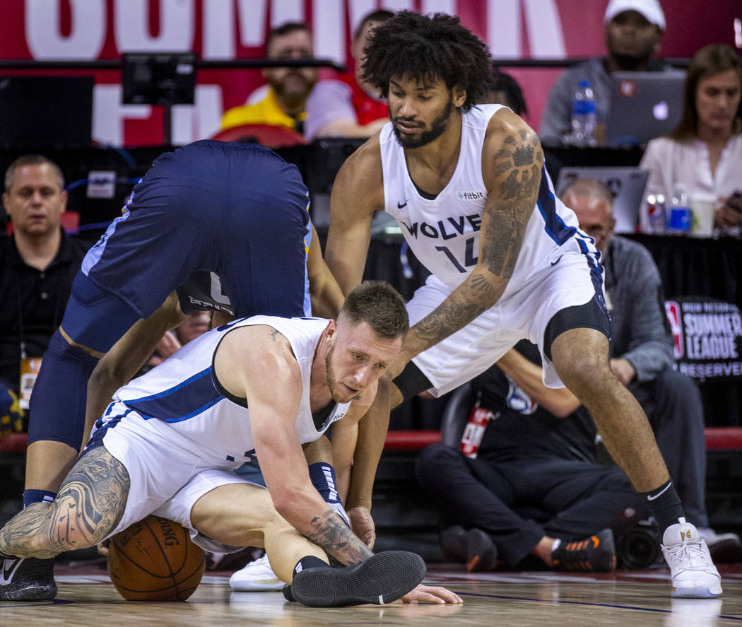 Minnesota Timberwolves forward Mitch Creek, below, sits on the ball after scrambling for it wit ...