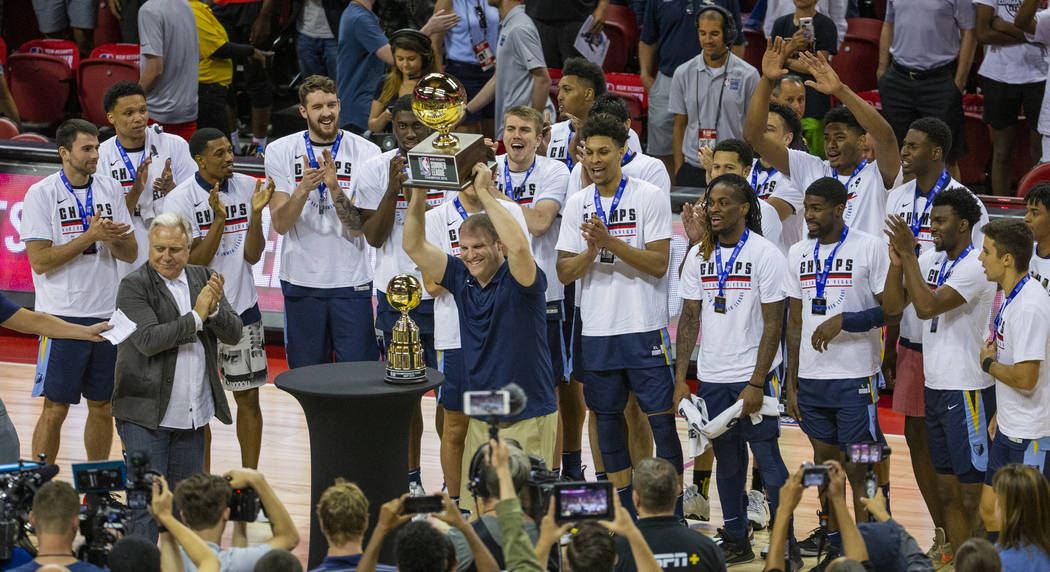 Memphis Grizzlies head coach Taylor Jenkins hoists the winning trophy after his team defeated t ...