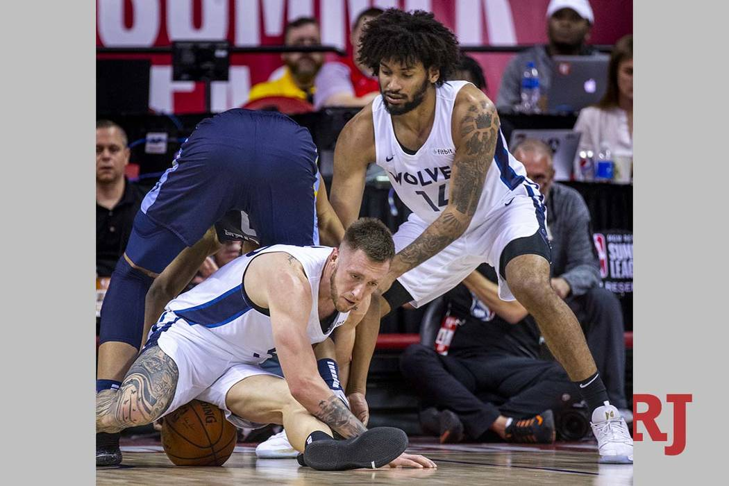 Minnesota forward Mitch Creek, below, sits on the ball after scrambling for it as Timberwolves ...