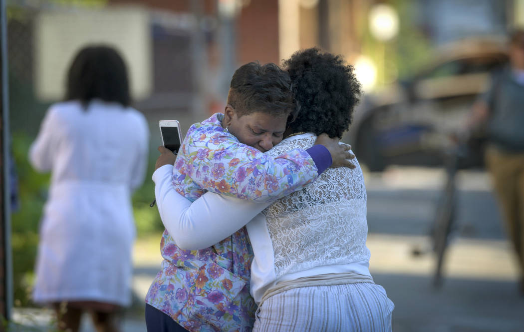 Two women embrace in an alley behind the Man Alive drug treatment center shortly after a shooti ...
