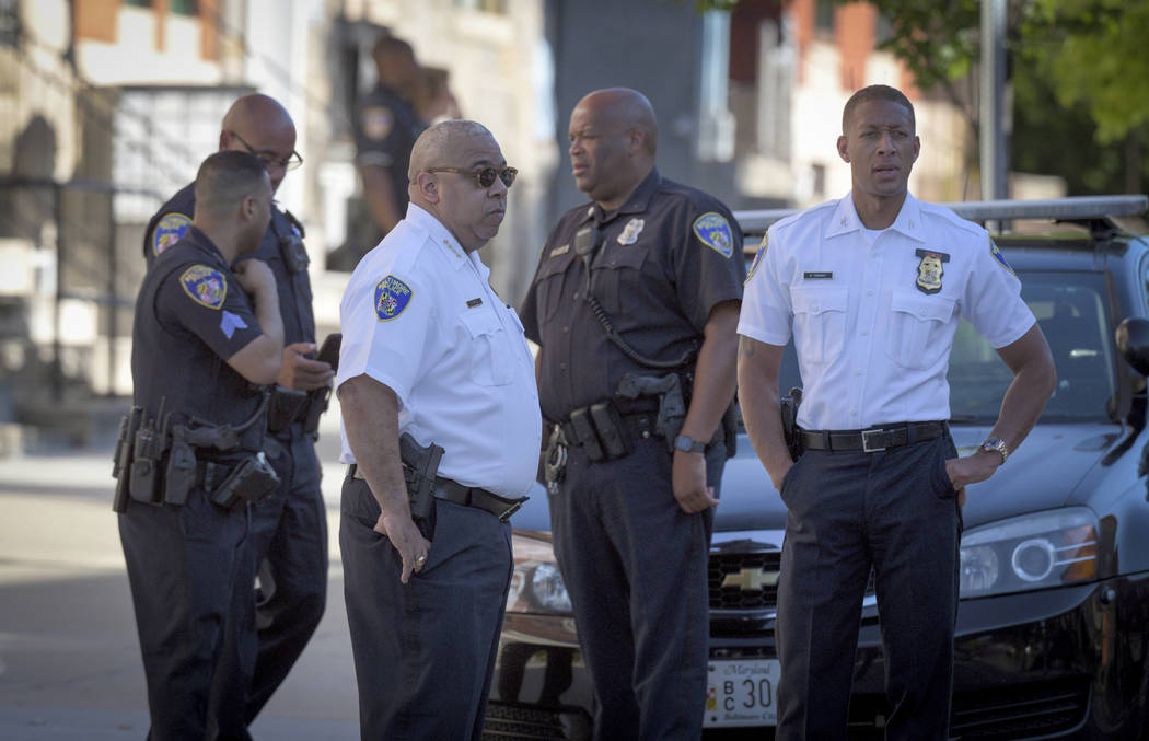 Baltimore Police commissioner Michael Harrison, center left, stands near the scene of a shootin ...