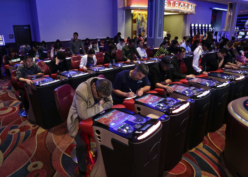 In this Oct. 3, 2014, file photo, visitors to the Resorts World Casino at the Aqueduct racetrac ...