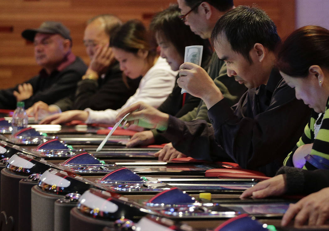 In this Oct. 3, 2014 file photo, a gambler slides a $100 bill into an electronic baccarat game ...