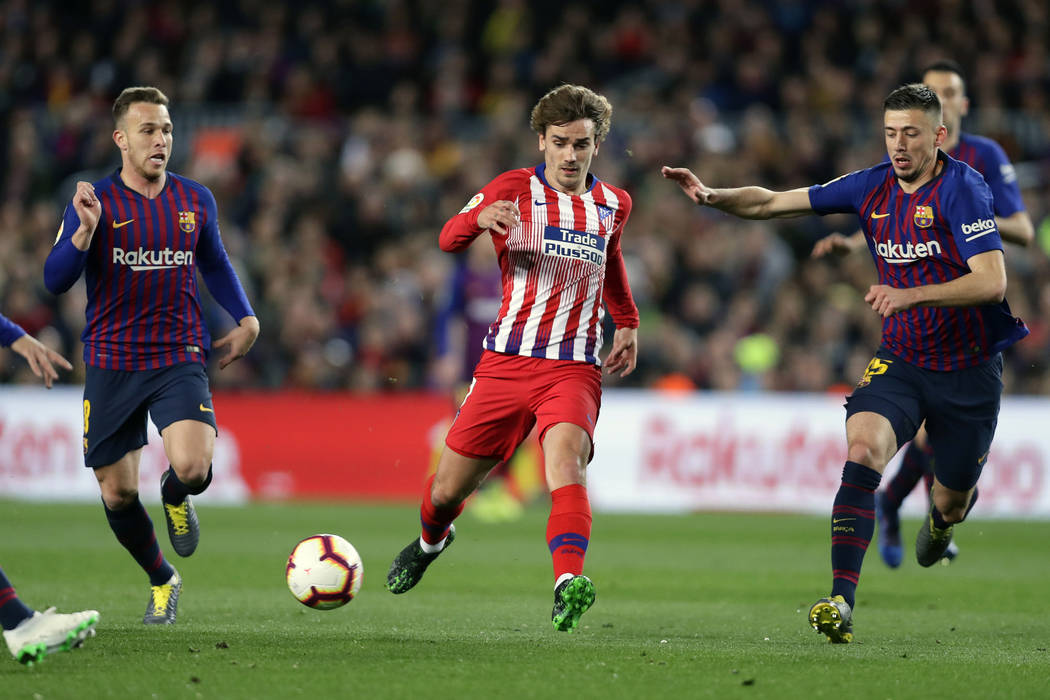 FILE - In this April 6, 2019, file photo, Atletico forward Antoine Griezmann, center, vies for ...