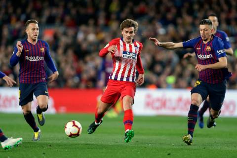 Atletico forward Antoine Griezmann, center, vies for the ball with Barcelona midfielder Arthur, ...