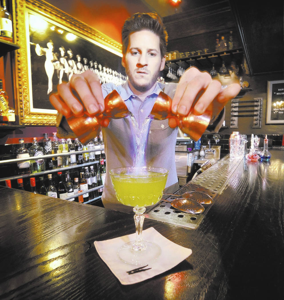 Laundry Room boozologist Dan Marohnic adds a flaming finish to a drink at the Commonwealth at 5 ...