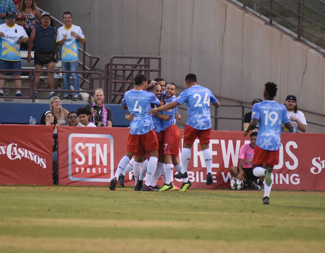 Lights FC players celebrate with Jesus Gonzalez, who scored his first goal on July 4 against LA ...