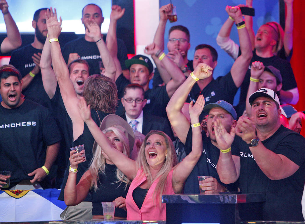 Fans of Alexander Livingston cheer him on at the main event final table at the World Series of ...