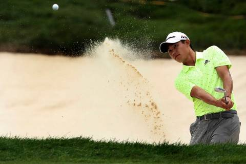 Collin Morikawa hits out of a bunker at 18 during the third round of the 3M Open golf tournamen ...