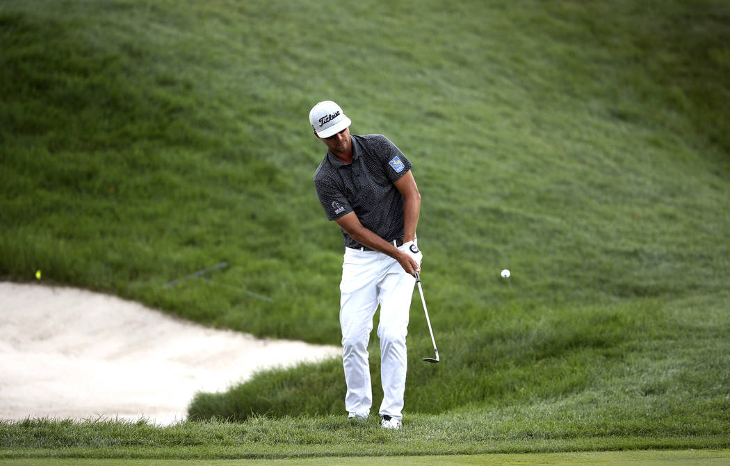 Collin Morikawa chips on the green at nine during the third round of the 3M Open golf tournamen ...