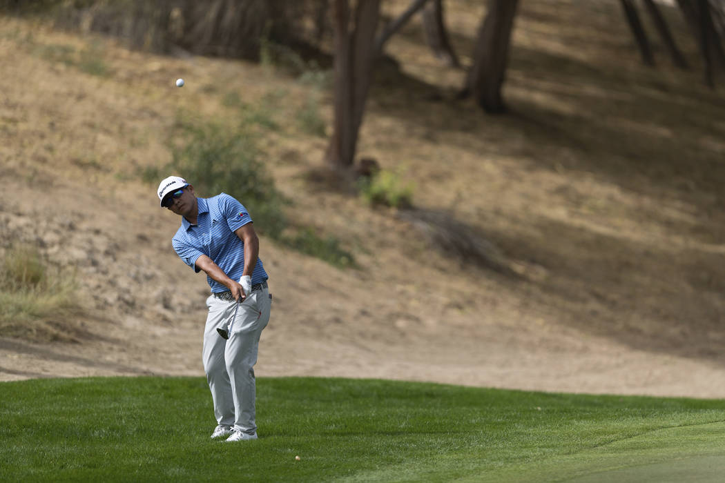 Kurt Kitayama of the U.S. chips onto the green on the 3rd hole during round one of the Dubai De ...