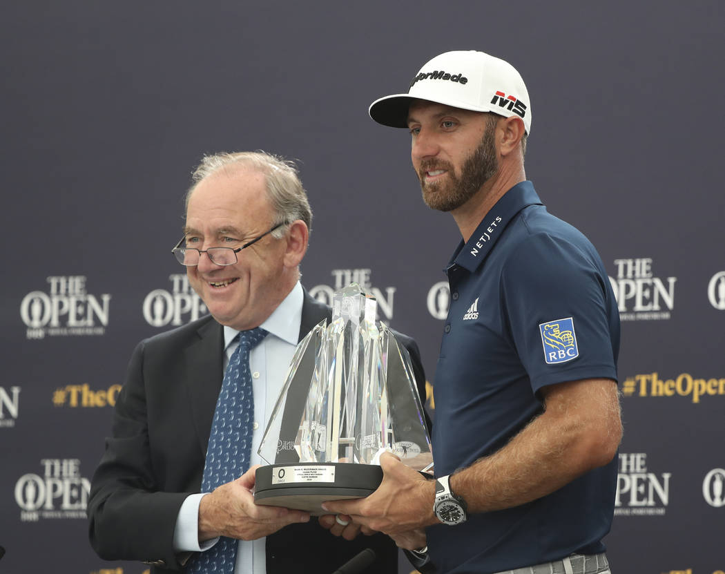 Dustin Johnson of the United States, right, receives The Mark H McCormack award for being the l ...