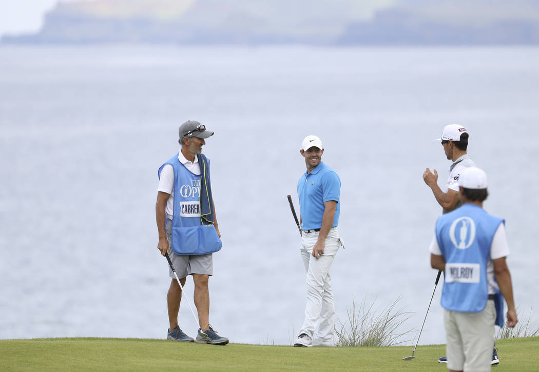Northern Ireland's Rory McIlroy, centre talks to Spain's Rafa Cabrera Bello, right, on the 5th ...