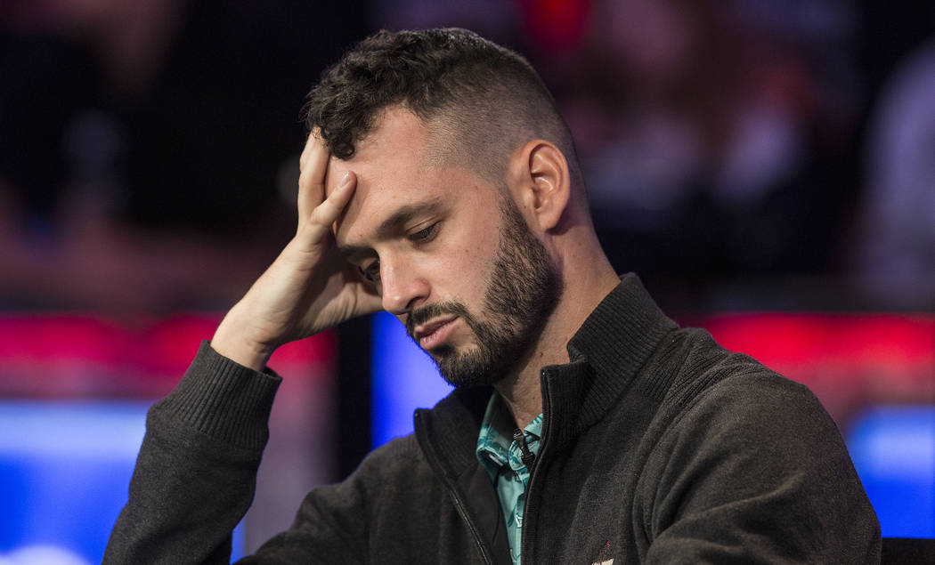 Alex Livingston, from Canada, looks at his cards during the World Series of Poker Main Event on ...