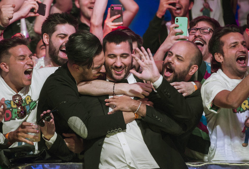 Dario Sammartino, middle, from Italy, celebrates with fans after advancing to the final two pla ...