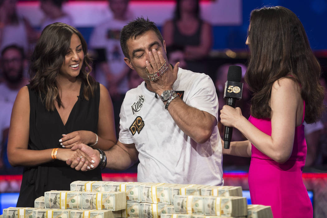 Hossein Ensan, middle, from Germany, kisses the championship bracelet after winning the World ...