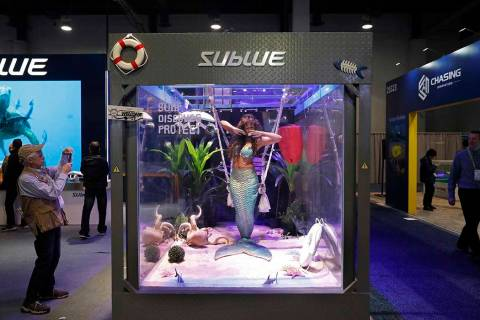 In this Jan. 9, 2019, file photo a woman dressed as a mermaid performs at the Sublue booth at C ...