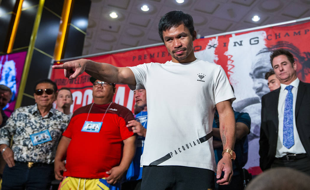 Boxer Manny Pacquiao points to the crowd during his grand arrival to the MGM Grand on Tuesday, ...