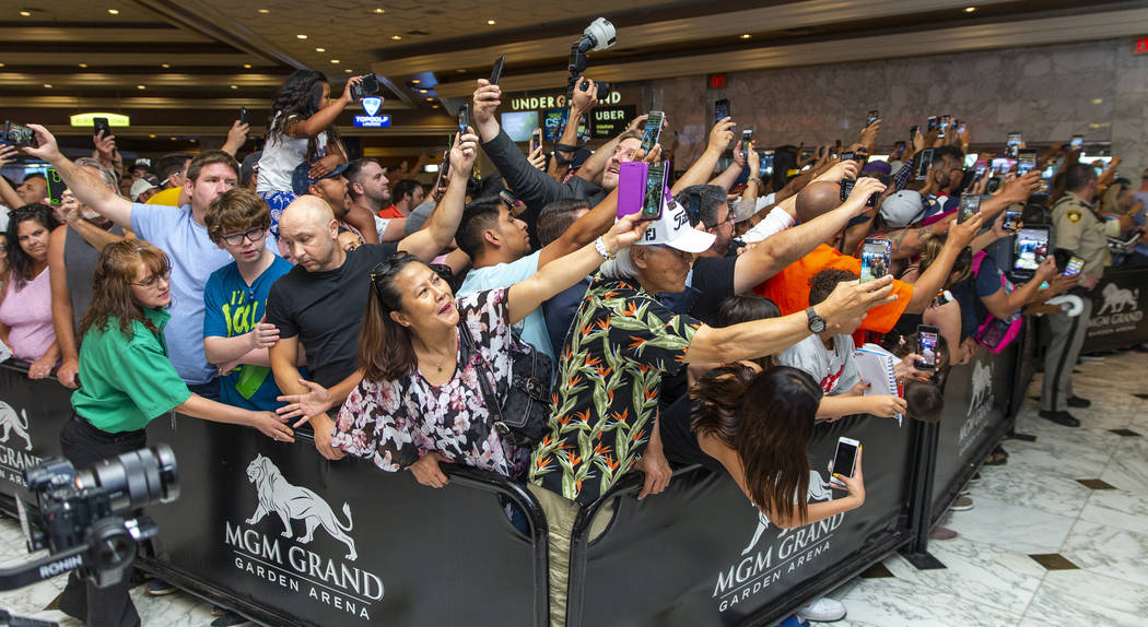 Fans push each other and ready their phones as boxer Manny Pacquiao enter the building during h ...