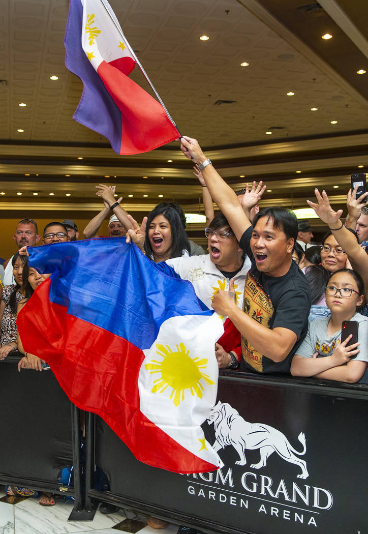 Fans (from left, center) Cherie and Darwin Custodio with Orly Manimtim join others in cheering ...