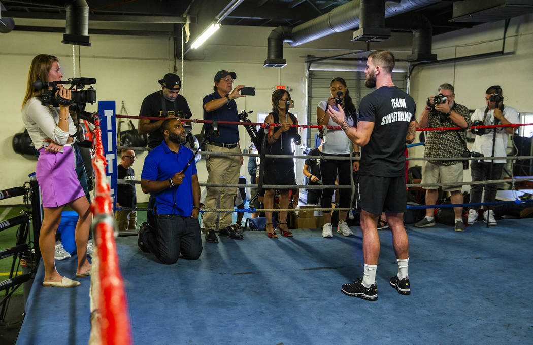 Boxer Caleb Plant, IBF super middleweight champion, center, gives an interview during a media d ...