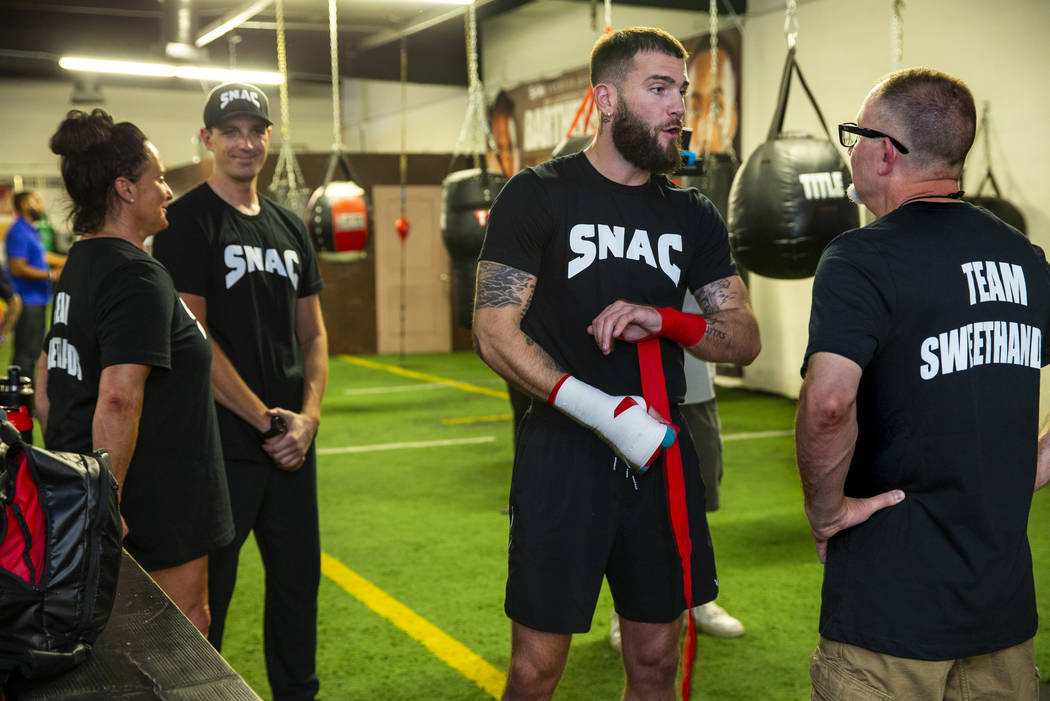 Boxer Caleb Plant, IBF super middleweight champion, center, confers with his father Richie Plan ...