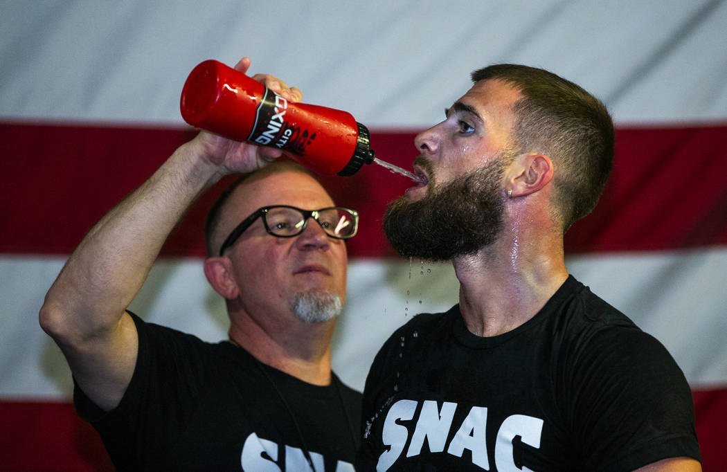 Boxer Caleb Plant, IBF super middleweight champion, right, is given some water by his dad Richi ...