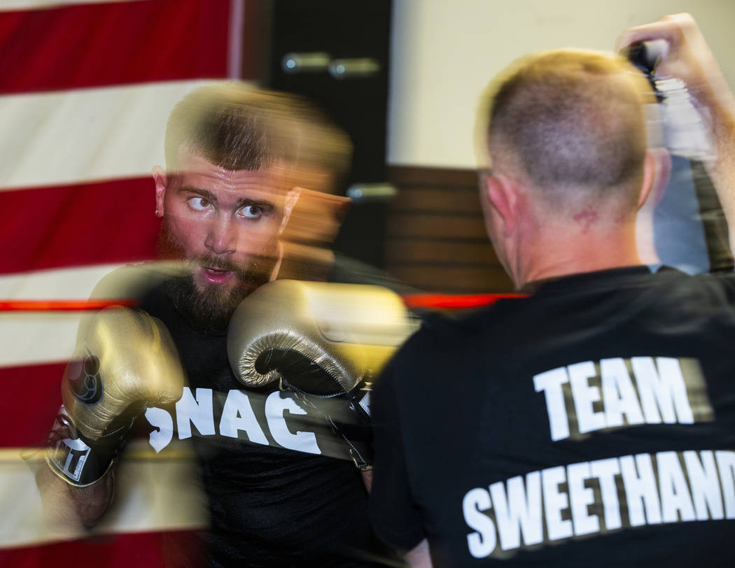 Boxer Caleb Plant, IBF super middleweight champion, left, readies to strike a pad held by his d ...