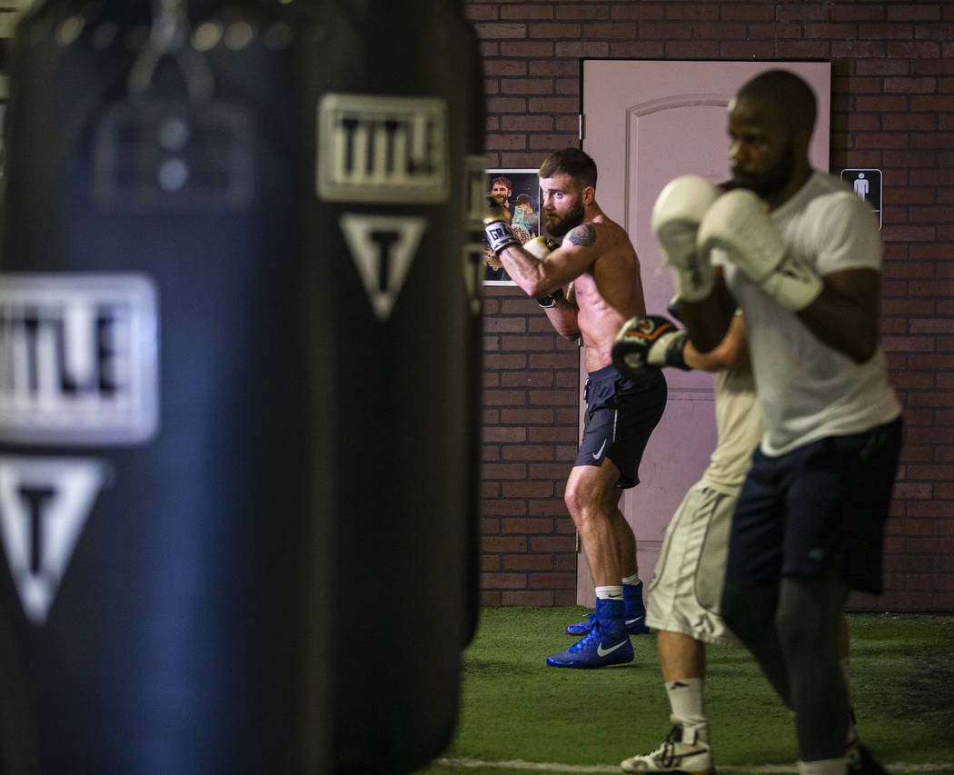 Boxer Caleb Plant, IBF super middleweight champion, rear, strikes the heavy bag during a media ...