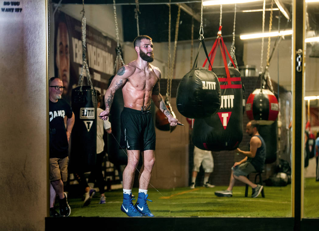Boxer Caleb Plant, IBF super middleweight champion, right, jumps rope as his dad Richie, left, ...