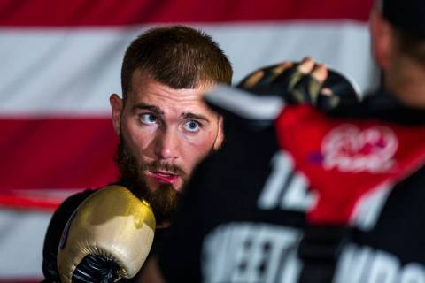 Boxer Caleb Plant, IBF super middleweight champion, punches a pad in the ring with trainer Just ...