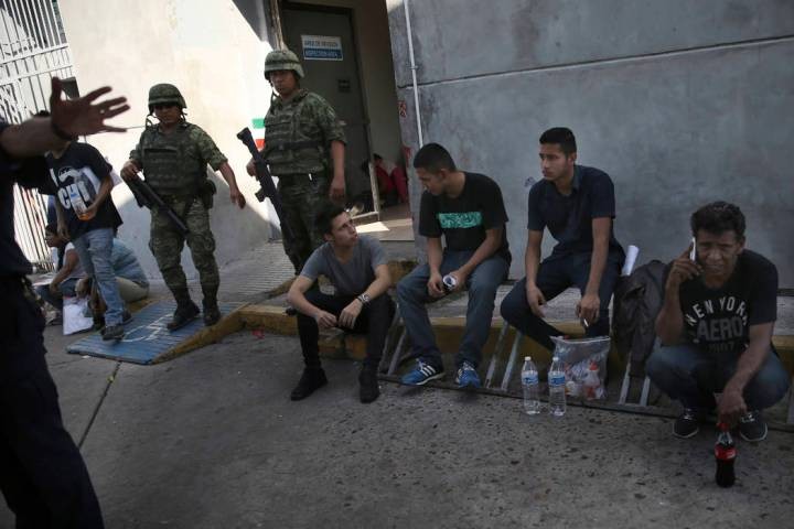 Migrants wait under guard at an immigration center on the International Bridge 1, as an immigra ...