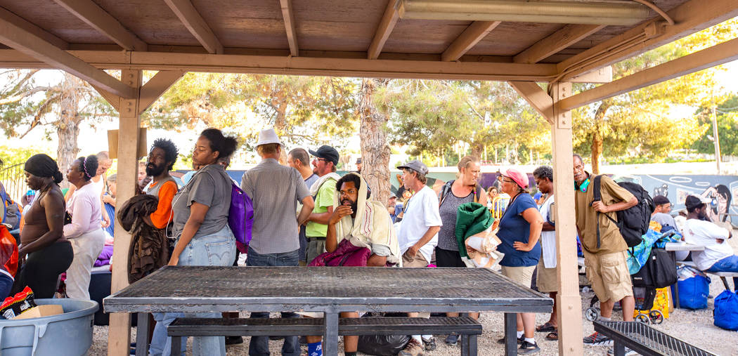 Residents wait in line for mattresses to sleep for the night at the Courtyard Homeless Resource ...