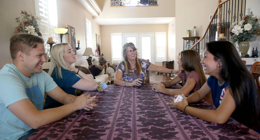 Anita Stephens, center, prepares for a card game with, from left, son-in-law Trevor Phillips, 2 ...