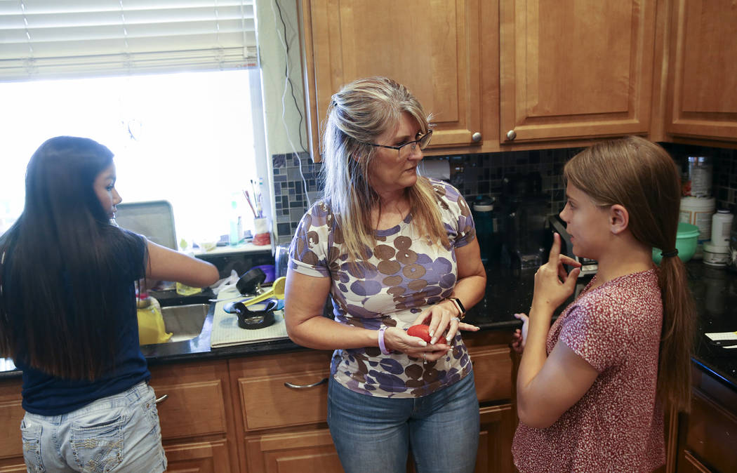 Anita Stephens, center, makes dinner with adopted daughters Serra Stephens, 14, left, and Abi S ...