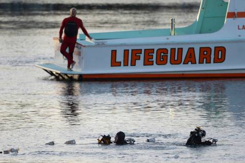 FILE - In this April 9, 2015 file photo, divers emerge from the water as debris believed to be ...