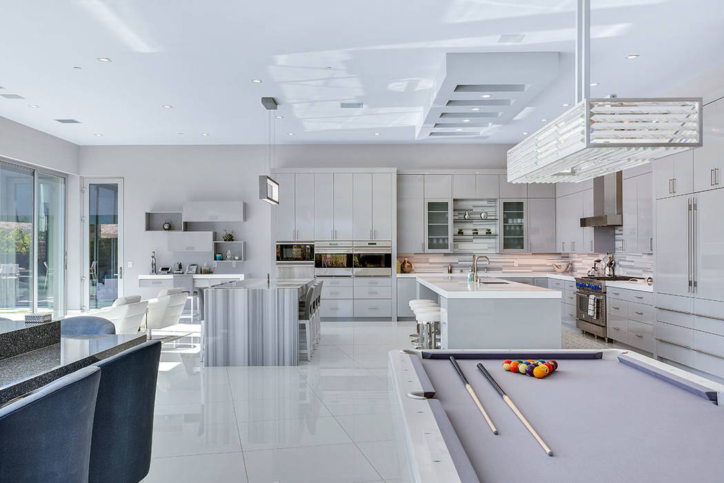 The kitchen leads into a living area, which has entertainment elements. (Ivan Sher Group)