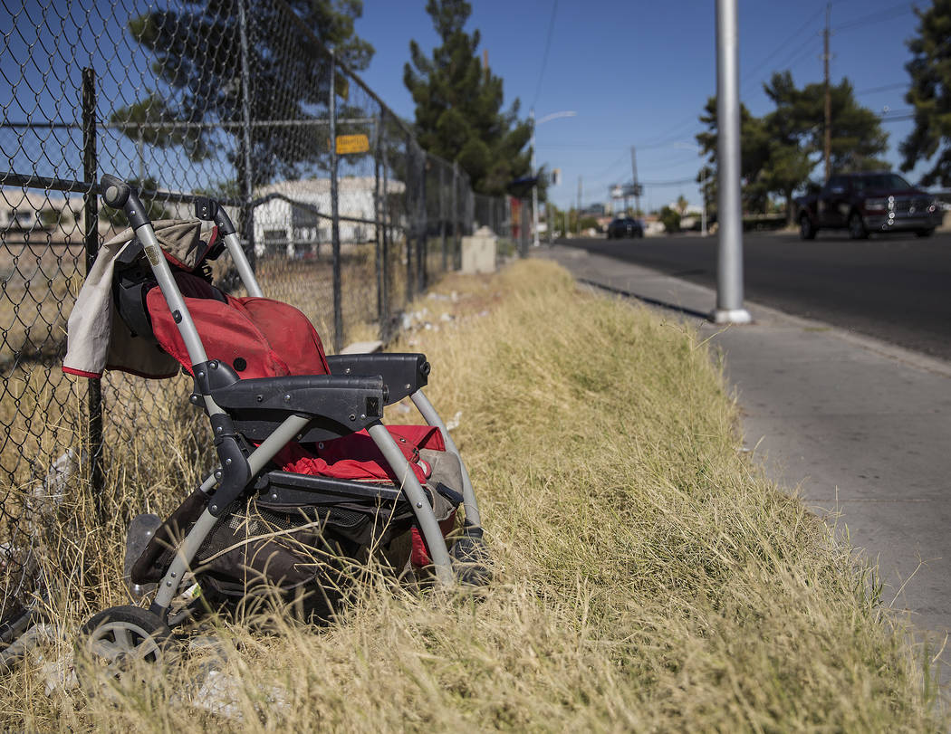 An abandoned baby stroller is propped up against a fence near the intersection of West Bonanza ...