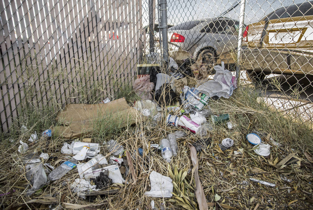 Trash and other debris pile up against a fence on West Bonanza Road near North Martin Luther Ki ...