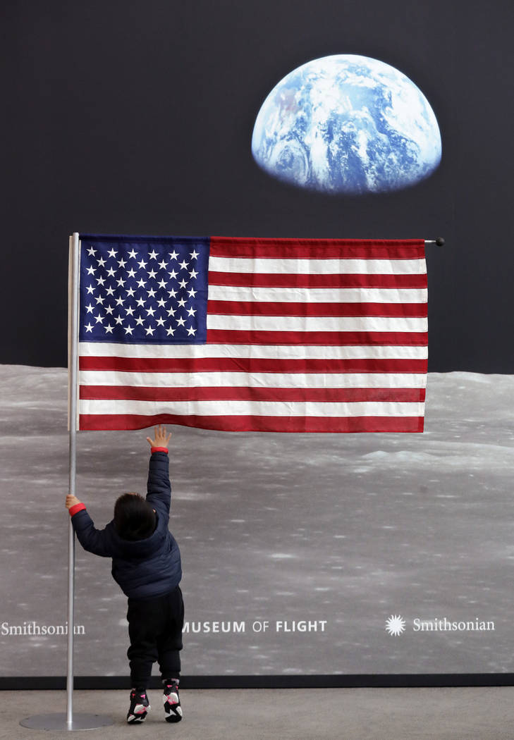 Guo JiuLe, 2, of Shanghai, China, reaches for a U.S. flag at the entrance of Destination Moon: ...