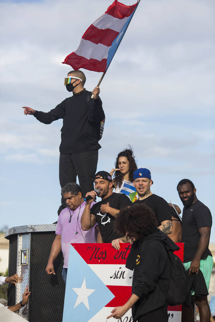 Singer Ricky Martin speaks to the crowd, accompanied by Puerto Rican rapper Rene Juan Perez kno ...