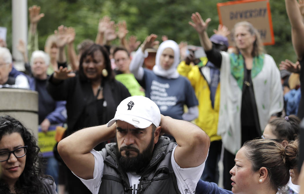 Jose Robles rests with his hands behind his head as supporters hold their arms toward him durin ...