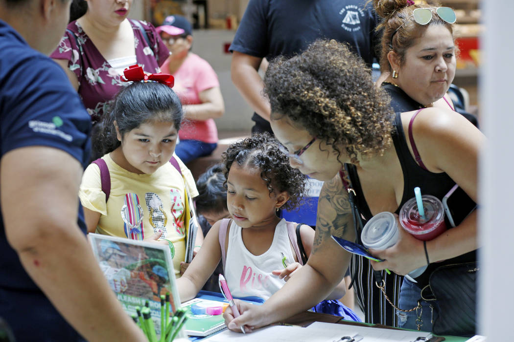 Families and students stop at the Girl Scout booth during the annual Cox Back to School Fair at ...