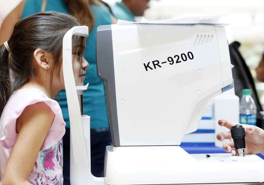 Lillian Daunas, 6, receives an eye check during the annual Cox Back to School Fair at the Galle ...