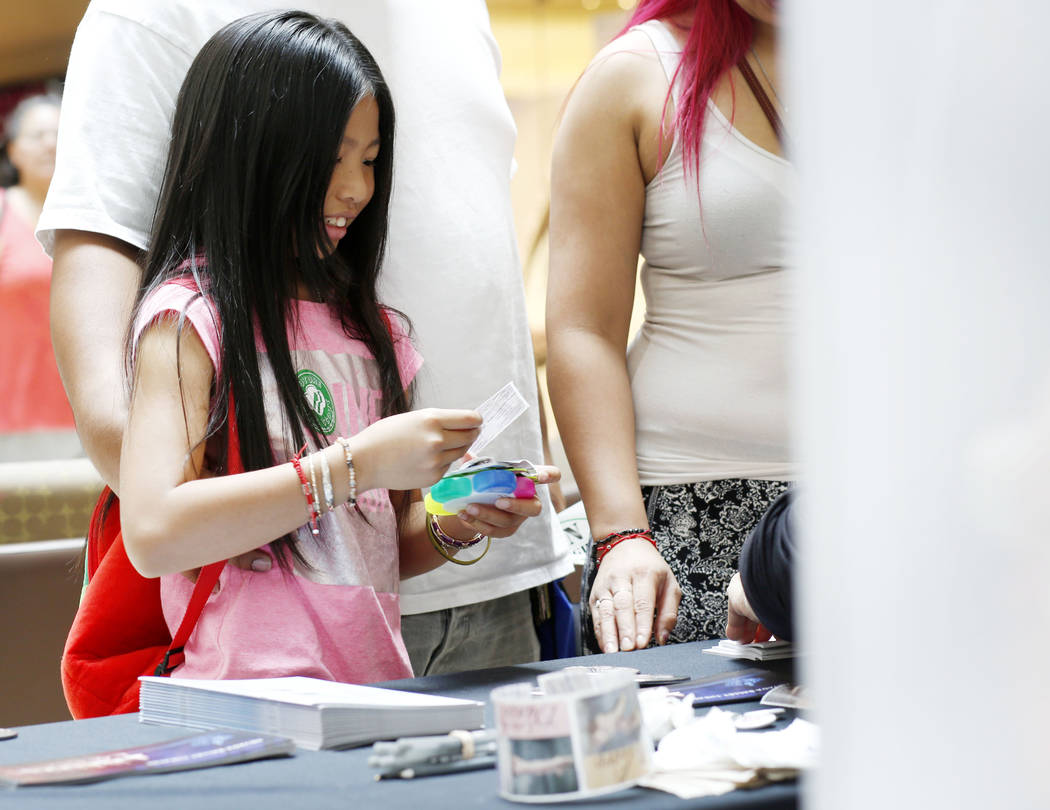 Ayane Nok, 9, new to Las Vegas, picks a sticker during the annual Cox Back to School Fair at th ...