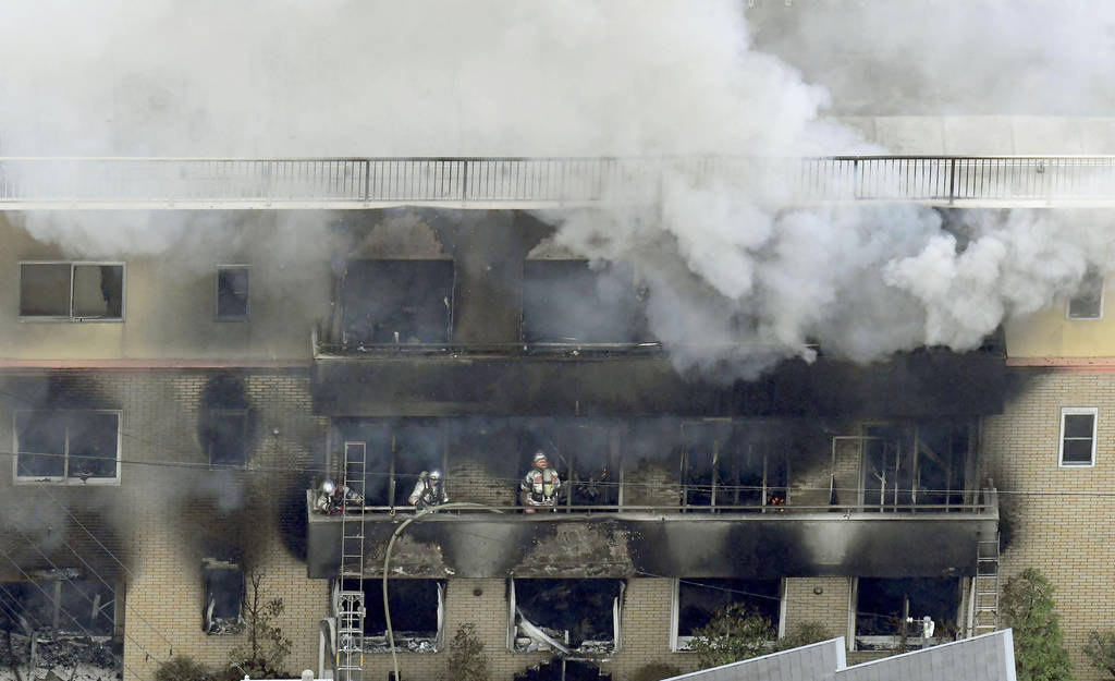 Firefighters work as smoke billows from a three-story building of Kyoto Animation in a fire in ...
