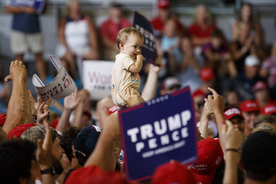 A baby is held high in the audience as President Donald Trump speaks at a campaign rally at Wil ...