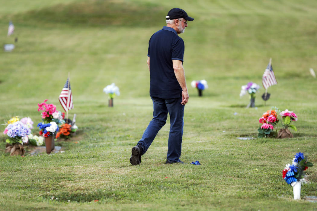 Eddie Davis walks past tributes on his way to his son Jeremy's gravestone, who died from the ab ...